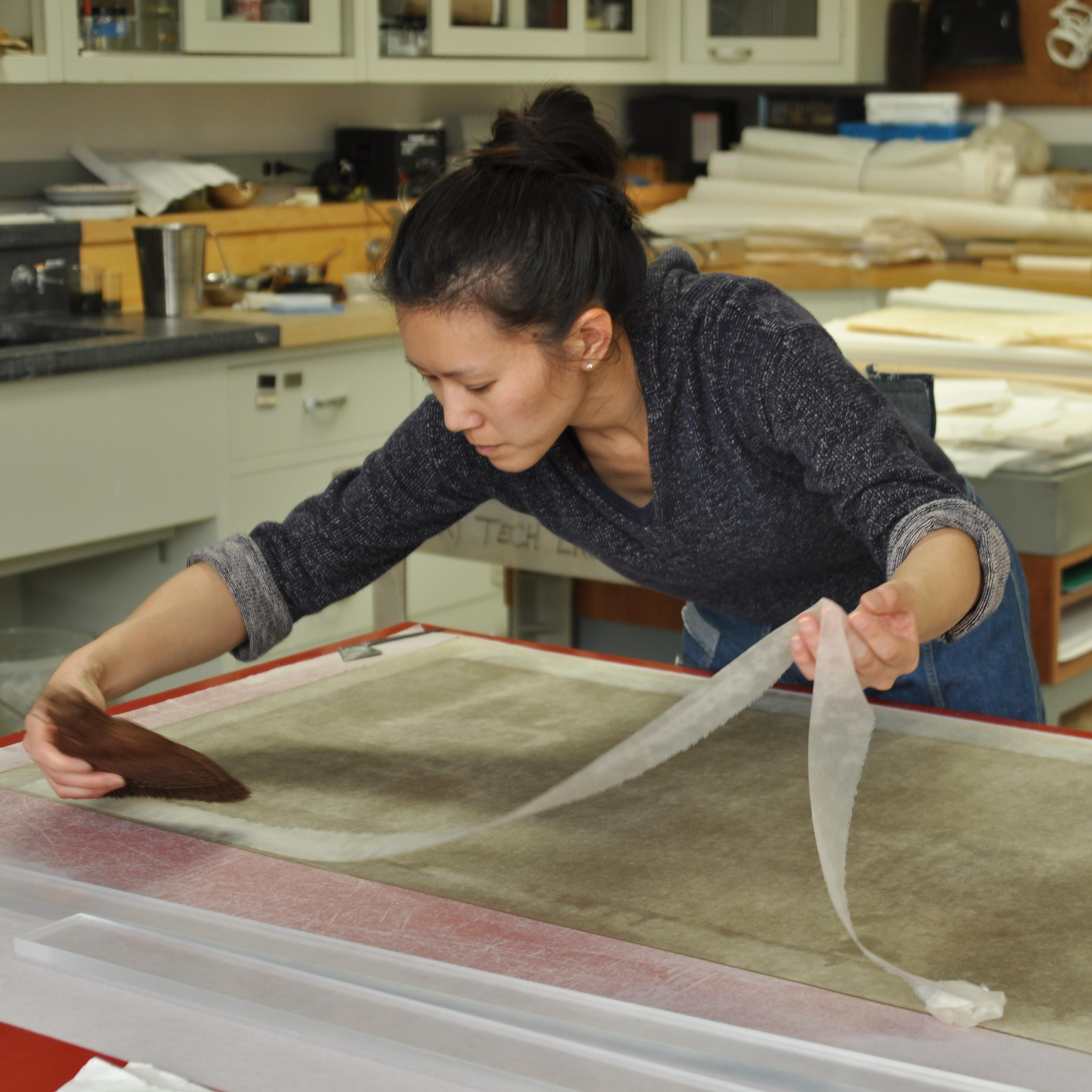 Grace Jan remounting a silk painting at the Freer|Sackler